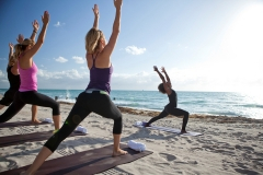 Tracie Wright Vlaun of V Art of Wellness leads an Aeroga (fast Yoga to a house music soundtrack) on the beach at The St. Regis Bal Harbour, Miami Florida.